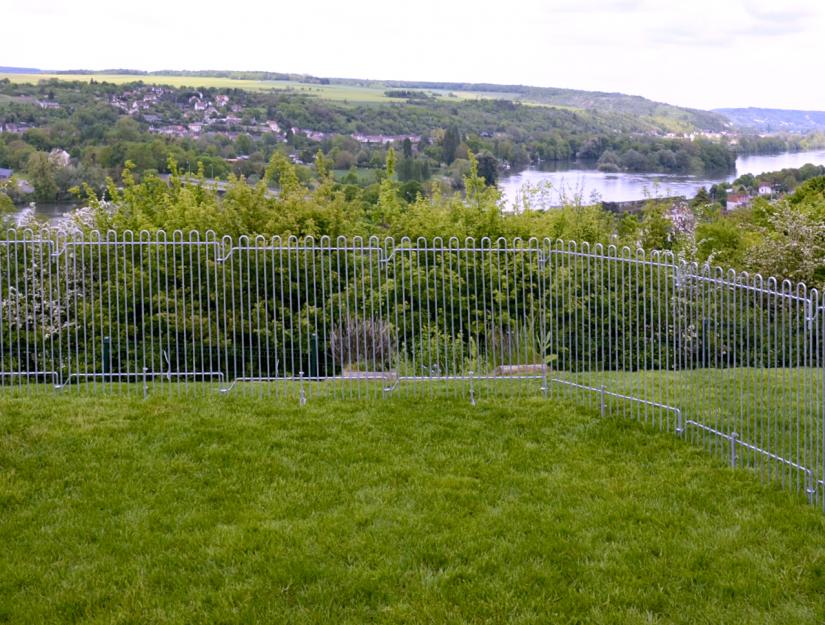 Clôture fixée dans la pelouse avec des piquets de stabilisations. Ici, les piquets sont très profonds dans le sol.