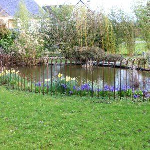 protection de bassin dans le jardin en printemps avec des fleurs près de l'étang