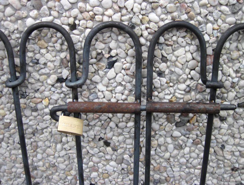 Als Kindersicherung sollten Sie ein Vorhängeschloss anbringen, welches die Öse des Federriegels sowie einen Zaunstab umschließt.