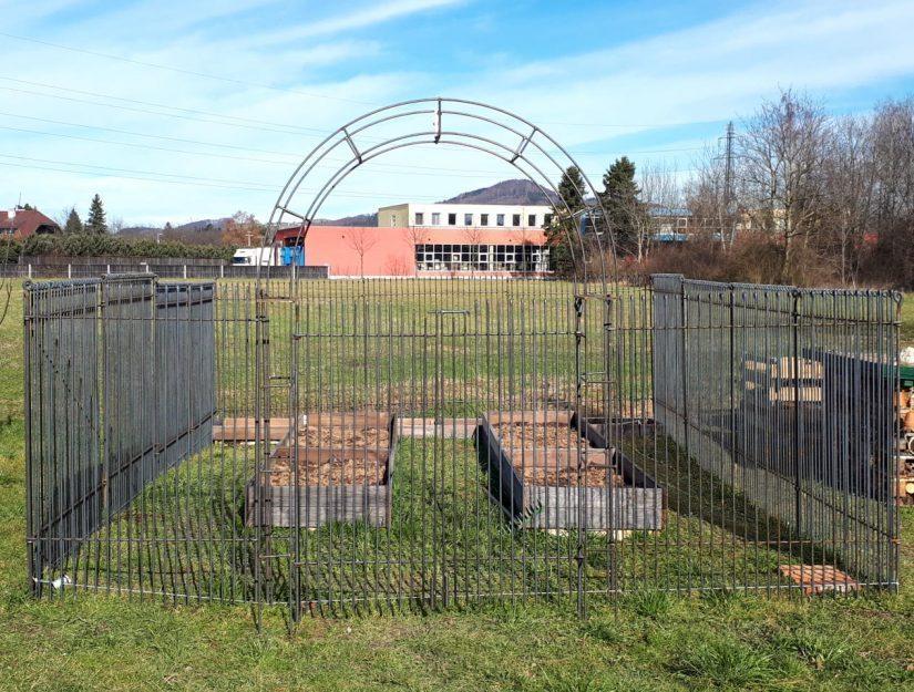 Arche de jardin avec double porte et clôture en acier brut.
