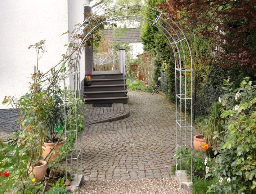 Der verzinkte Rosenbogen überspannt den Weg im Garten.