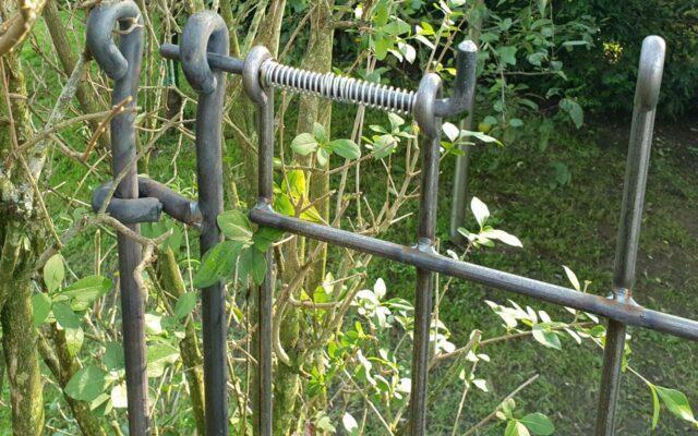 Gartentor in der Lücke einer Hecke aufgebaut