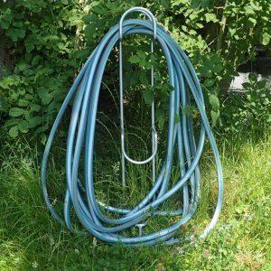 Gartenschlauch über Halter aus Metall aufgehangen