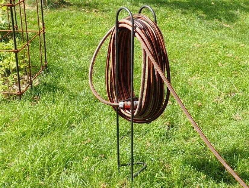 Porte-tuyau en métal (brut) avec tuyau d'arrosage Vue de l'arrière.