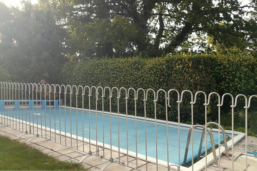 Das Schwimmbadgitter um den Außenpool aufgestellt.