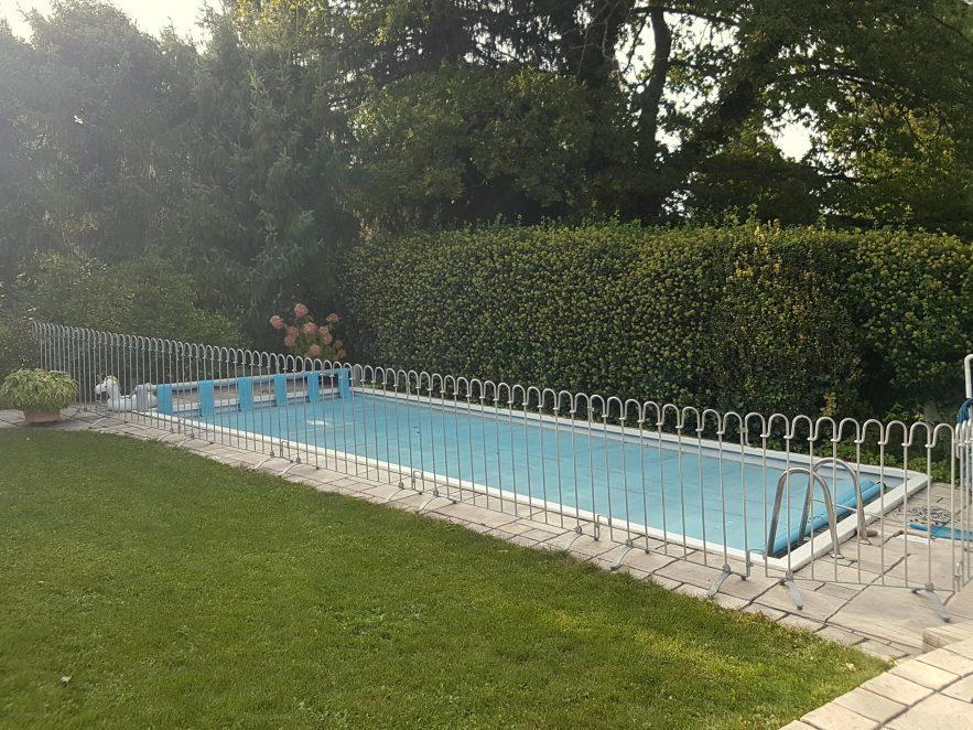 Schwimmbad mit aufgestellten mobilen Zaun als Kinder-Schutz.