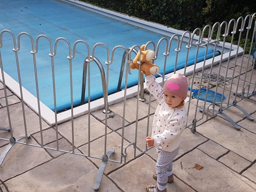 Kindersicherer Schwimmbadzaun um den Pool gestellt, das Kind kann nicht zum Wasser.