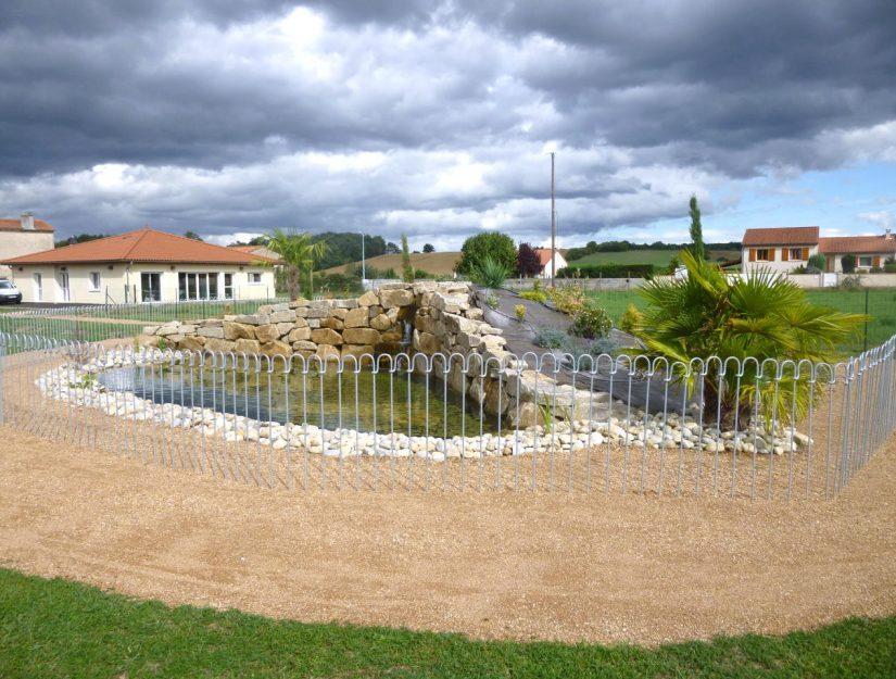 Barrière en fer galvanisé autour d'un étang avec un palmier en France.