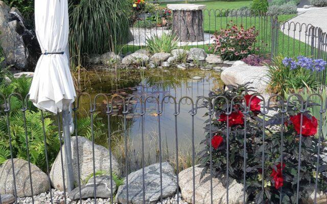 Steckzaun für einen Teich mit Blumen