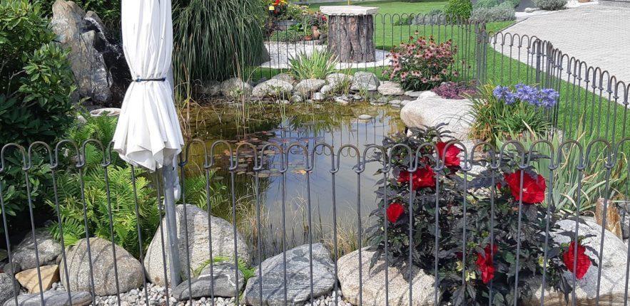 Der Teich mit den Blumen hat eine Kindersicherung aus einzelnen Stahlstäben.