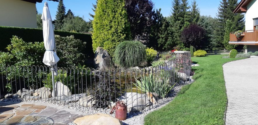 Zwischen der Terrasse und dem Gartenteich ist ein Steckzaun im Boden eingesteckt.