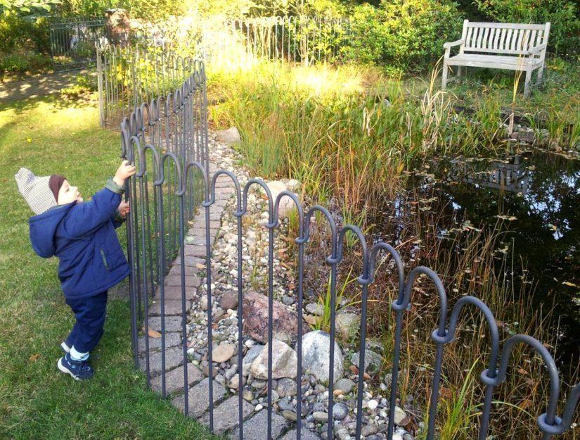 Kindersicherer Zaun um den Gartenteich. Das Kind kann nicht zum Wasser.