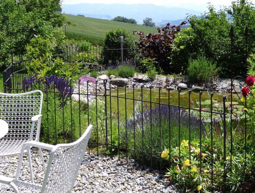 Durch dem Gartenzaun aus Metall können die Hunde und die Kinder nicht in den Gartenteich.