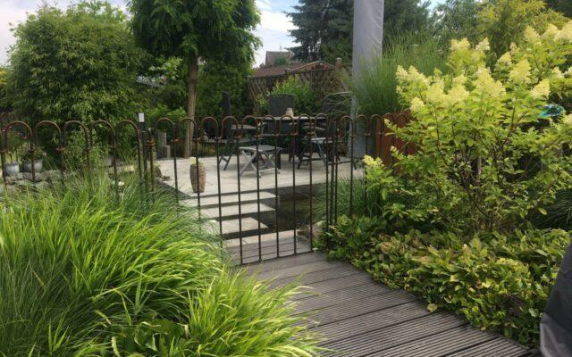 Bögen aus rostigem Stahl schützen den Teich