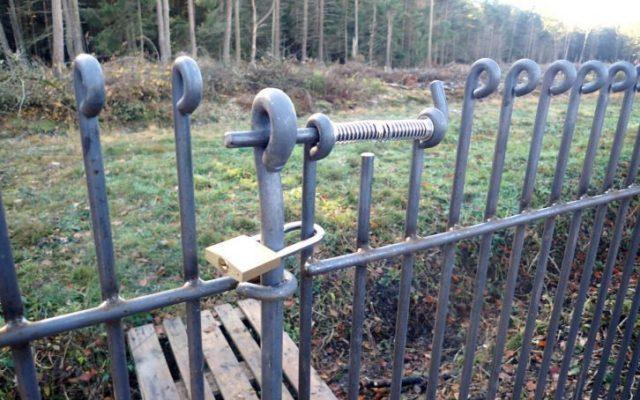 Tür vom Hundezaun mit einem Vorhängeschloss sichern