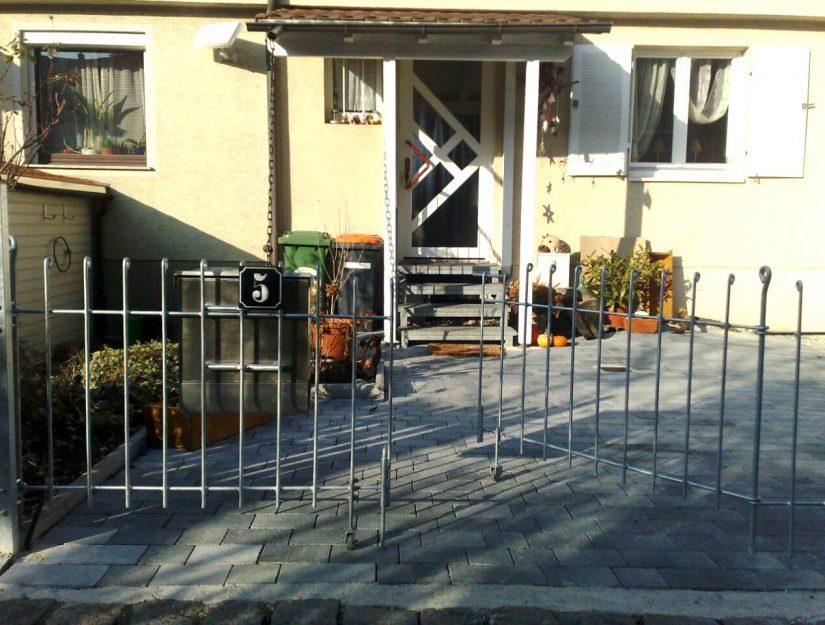 Doppelflügeliges Tor anneau-80-verzinkt (rostet nicht) vor einem Hauseingang.