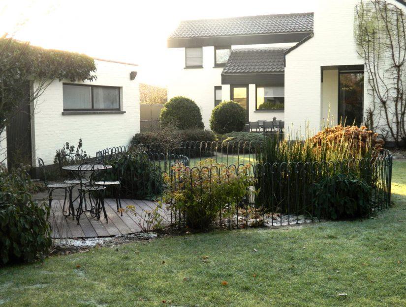 Coin repas sur la terrasse près d'un étang avec une clôture en métal.