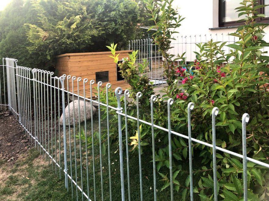 Steckbarer Welpenfreilauf aus verzinktem Stahl um die Hundehütte aufgestellt