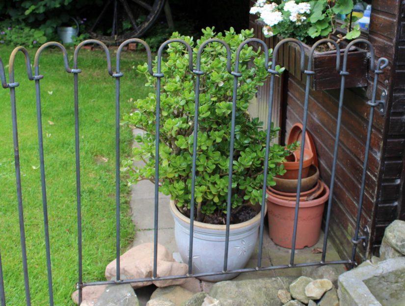 Das Bachlaufelement ist mit zwei Wandhaltern an einem Gartenhaus befestigt.