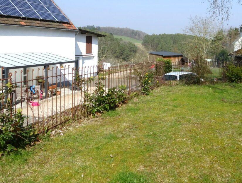 Rostiger Eisen-Steckzaun vor einem Mauerabsatz an einem Bauernhof.