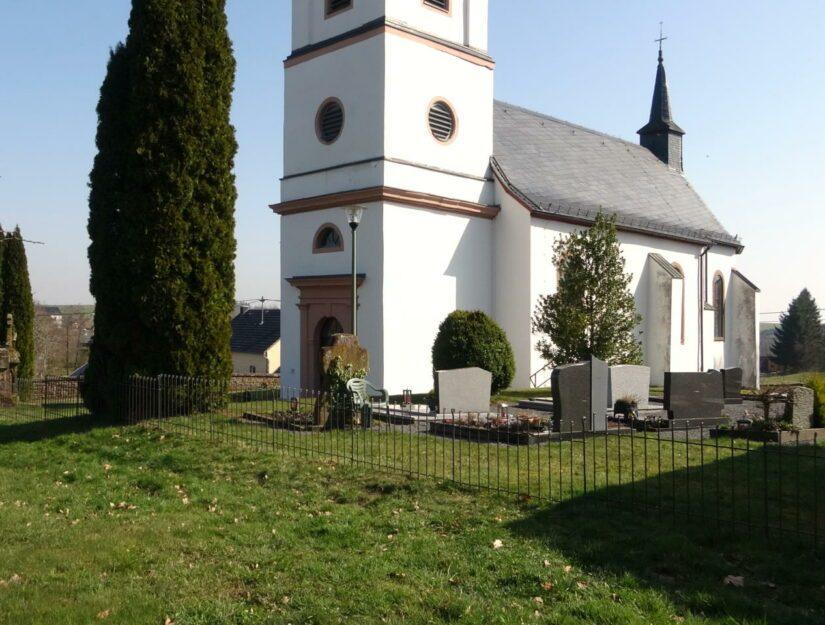 In den Boden gesteckter Friedhofszaun vor einer Kirche in der Eifel.