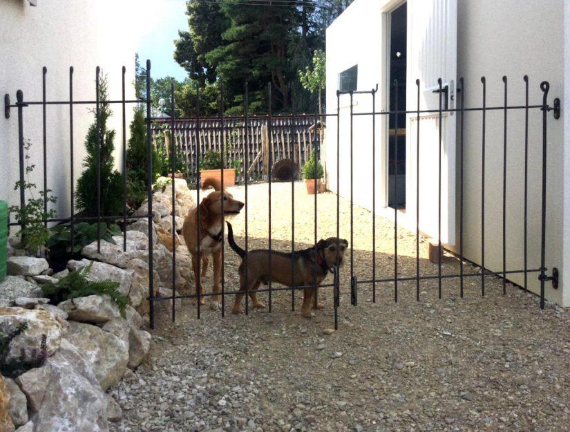 Le portail à double battant entre deux parois est maintenu en place par des supports muraux avec des pinces pour fixation.