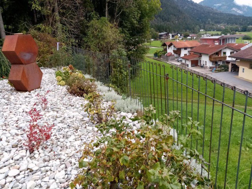Der Zaun steht am Hang vor der Wiese hinter den weißen Kieselsteinen.
