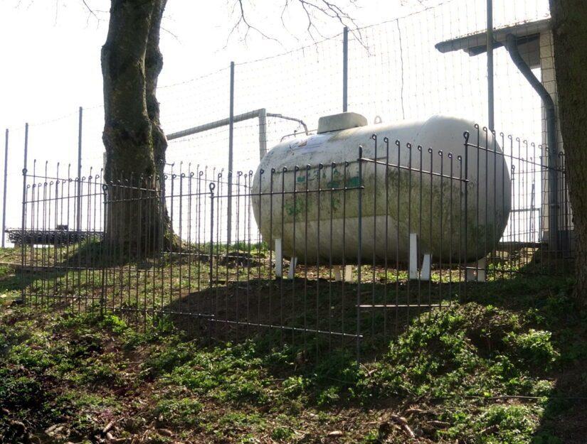 Gesteckter Zaun um einen Gastank neben einem Fußballplatz.