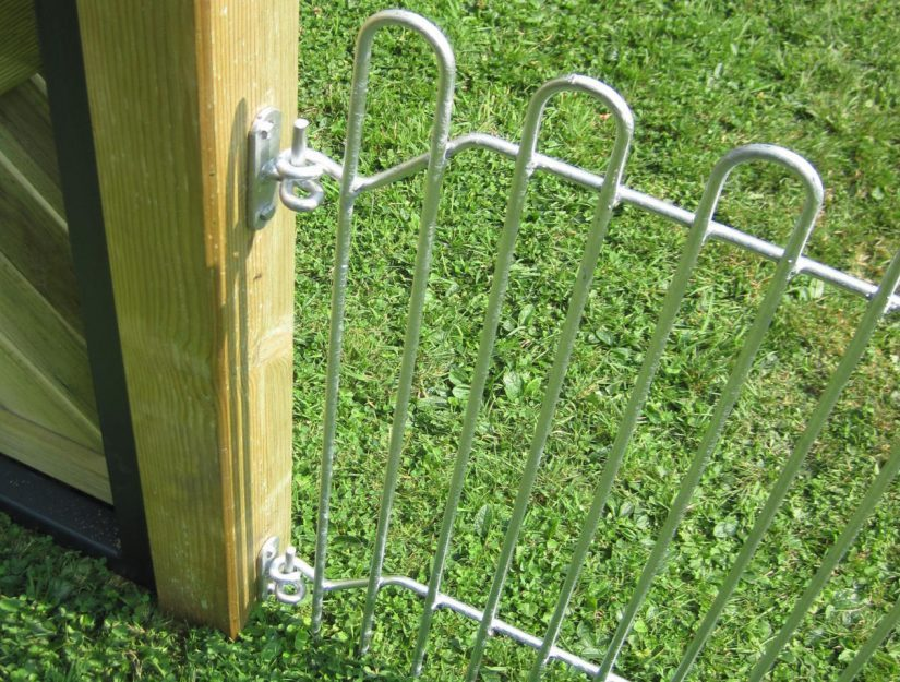Hier ist der Wandhalter andersrum am Holzpfosten geschraubt. Dadurch kann die Seite mit der Gitter-Öse am Pfosten befestigt werden.