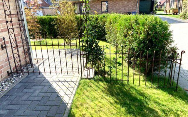 Zaun mit Tor am Haus befestigt