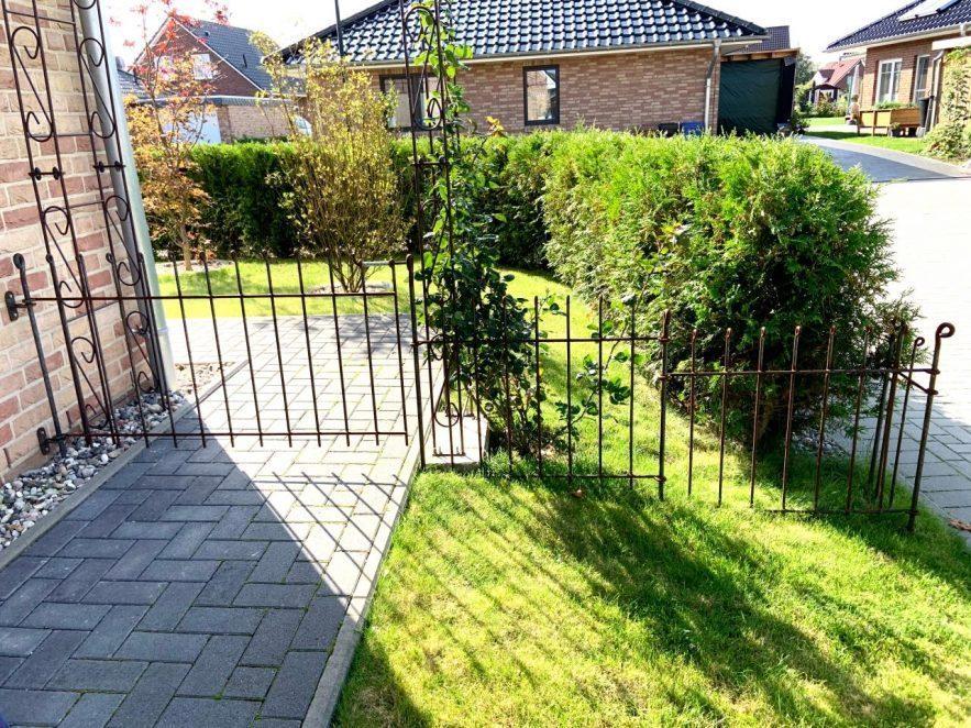 Die Zauntür ist mit Wandhalter am Haus befestigt. Der Zaun gleicht Stufenförmig das Gefälle aus.