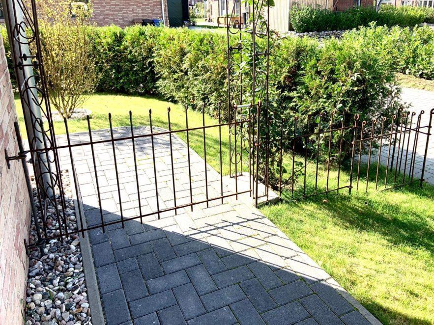 Rostiger Zaun neben dem Haus, mit einem Tor über dem Weg vor dem Rosenbogen.