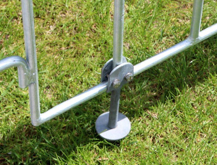 Ein Boden-Einsteckstift am poolfix-Gitter angeschraubt im Rasen eingesteckt.