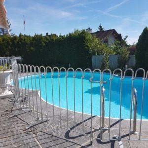 Metallzaun steht auf der Terrasse vor einem Pool