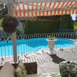 Der kindersichere Metallzaun steht auf der Terrasse vor einem Pool.