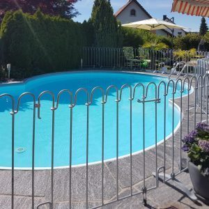 Der verzinkte Metallzaun steht auf der Terrasse vor einem Pool.