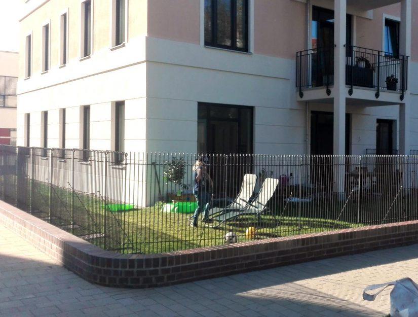 Zaun im Vorgarten von einem einem Wohnblock in der Stadt.
