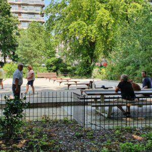 Il y a un terrain de pétanque clôturé dans un grand parc bruxellois.