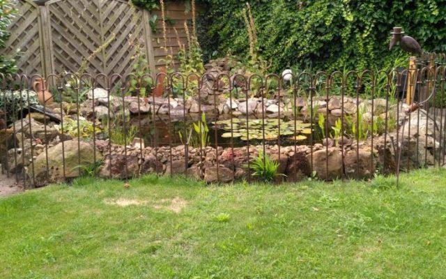 Rostiger Teichzaun um einen kleinen Gartenteich
