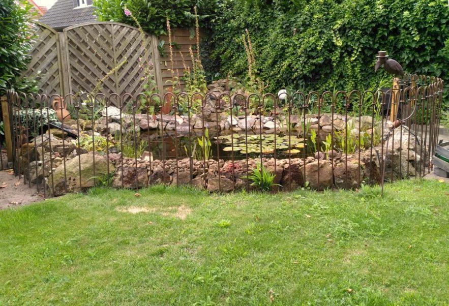 Brauner rostiger Teichzaun im Garten als Schutz für die Kinder