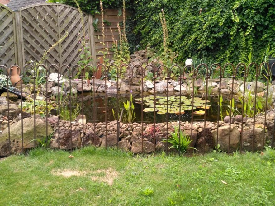 Rostender Zaun um einen kleinen Gartenteich