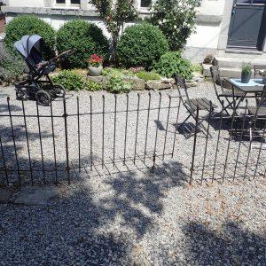 Die Steckzaun-Tür ist leicht geöffnet und auf einer Bodenrolle abgestützt