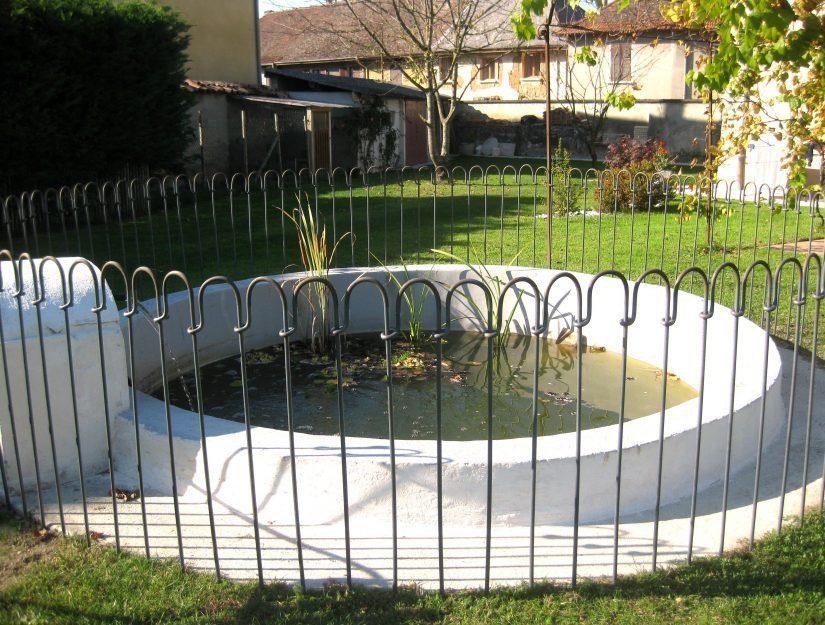Steckzaun als Kindersicherung vor einem runden Wasserbecken.