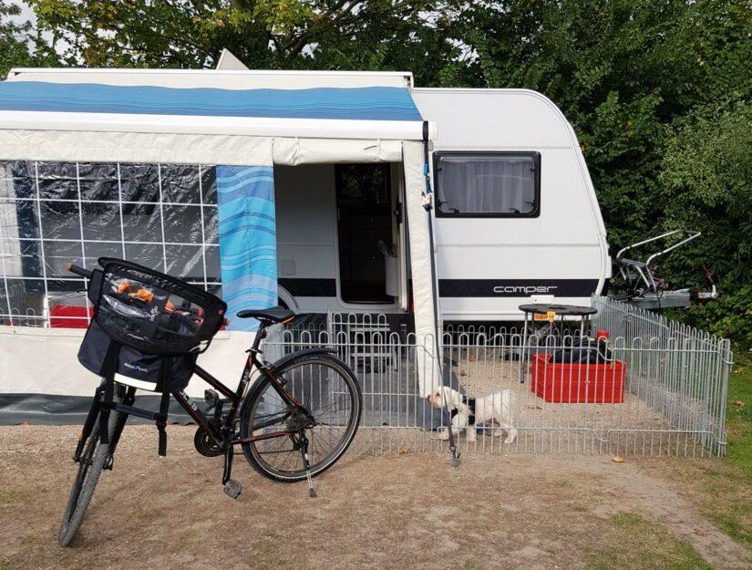Zaun als Hunde-Gehege vor einem Wohnwagen auf dem Campingplatz.